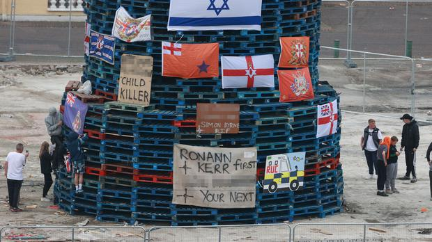 Flags and banners are hung on a large bonfire being built to mark the Catholic Feast of the Assumption in the Bogside area of Londonderry (Liam McBurney/PA)